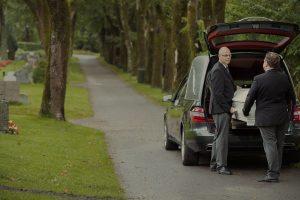 To menn utfører kistetransport hos Jølstad